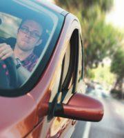 man driving red car
