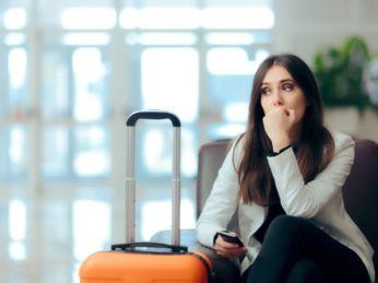 sad woman sitting with suitcase