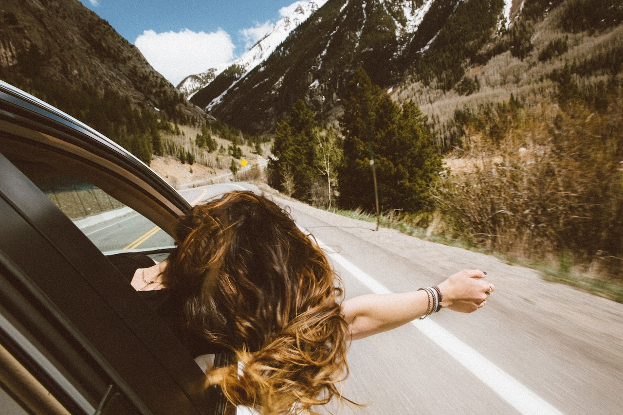 girl leaning out the car window in the mountains to refresh energy